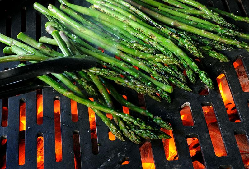 Asparagus grilling over a charcoal fire