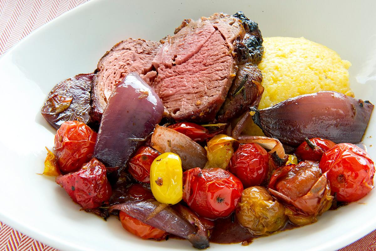 Image of Spit-roasted Leg of Lamb over Grits and Tomatoes